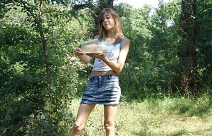 Cute young girl in denim skirt undressing outdoors to smear food on her body