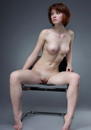 Nude skinny Bretta A poses on a studio chair showcasing her small perky tits